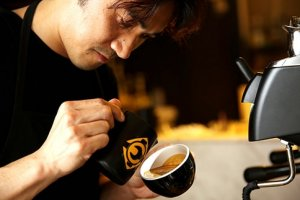 Barista trainer Masa Aoki demonstrates how free pour latte art is done. — Picture by Choo Choy May