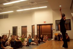Students sit on the floor of a dance classroom watching OCU professor of dance Jo Rowan teach.